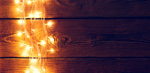 Image of wooden surface with burning garland on side.