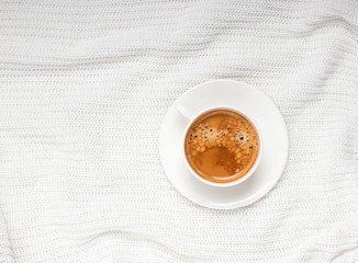 Cup of cofee onthe white knitted background