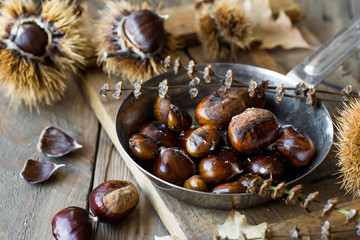 Roasted chestnuts in cast iron grilling pan over rustic wooden board and grey wooden background, selective focus, vertical composition, Fried Chestnuts