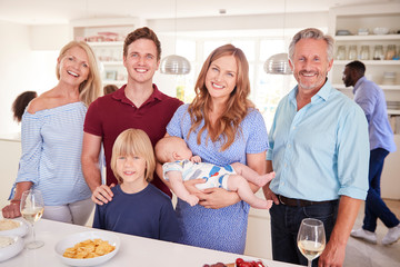 Portrait Of Multi-Generation Family And Friends Gathering In Kitchen For Celebration Party