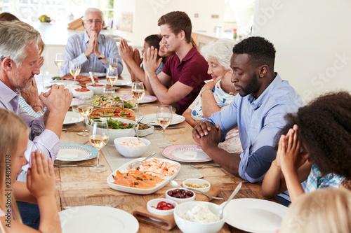 family praying around table - 700×467