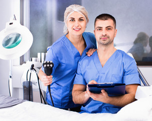 Portrait of two professional cosmeticians in modern medical esthetic office