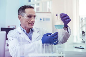 Cheerful young man working in laboratory at project