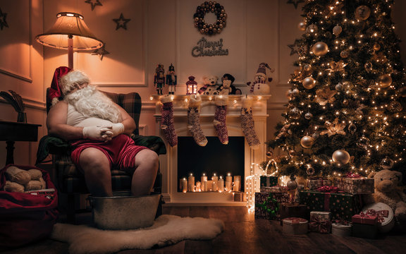 Santa Claus relaxing after or before work in cozy christmas room