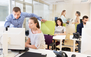 Businessman helping female colleague in work with computer