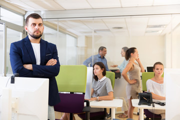 businessman with arms crossed in busy modern coworking space