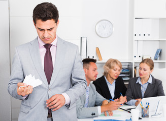 Irritated businessman in office with working associates
