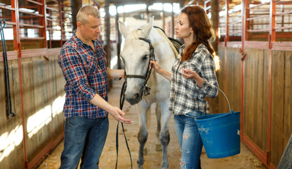 Couple with bucket before cleaning horse while standing at stabling