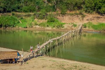 Two people on the bamboo bridge over the Nam Kahn River in Luang Prabang, Laos