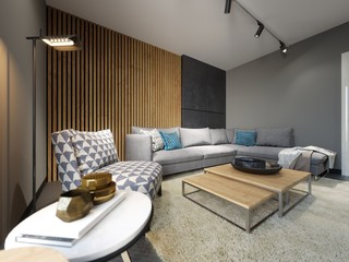 Modern loft interior of living room, grey sofa and colorful pillows on metal flooring and dark concrete wall and wood planks element .
