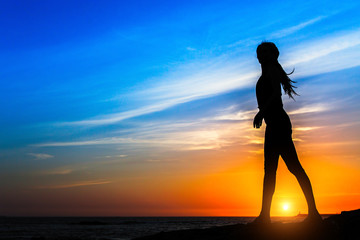 Silhouette of young woman on the sea coast during amazing sunset.
