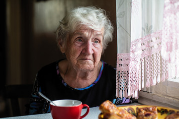 Retired elderly woman in the kitchen of his house sitting at the table.