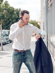 Thoughtful businessman with jacket and smartphone