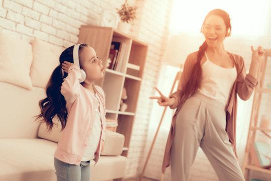 Girl and Smiling Woman in Pajamas Dancing at Home.
