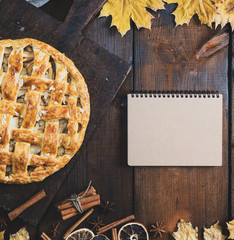 baked apple pie on a board and a notebook with a blank page for writing a recipe