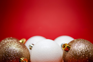 Set of golden and white Christmas tree decorations on a red background