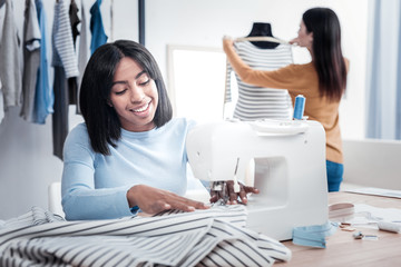 Delighted nice woman sewing clothes