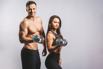 Athletic man and woman with a dumbells isolated over white background. Personal fitness instructor....
