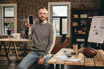 cropped view of casual businessman holding smartphone with blank screen in loft office