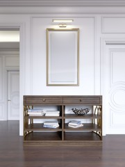 Classic wooden open console against the wall, with shelves and books and a picture with light over.