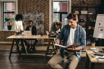 young man looking at journal in modern loft office with colleagues working on background