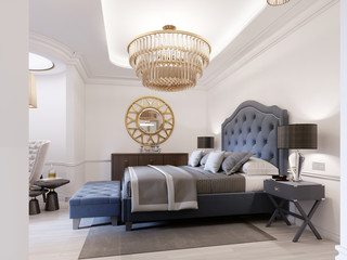 Modern bed in classic blue style with bedside table and lamp. Large glass chandelier over. A dresser with a decor and a golden mirror above. Modern bedroom.