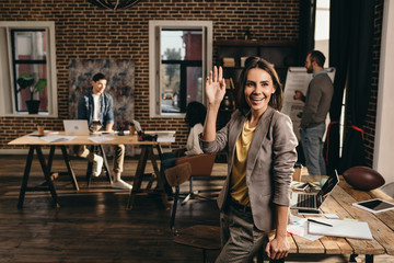 smiling business woman waving with hand at loft office with colleagues on background