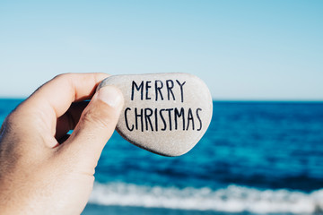 man holding a stone with the text merry christmas
