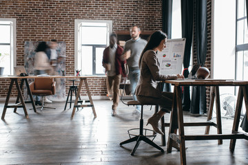 casual businesswoman working at desk with colleagues in motion blur in modern loft office