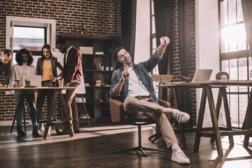 casual businessman taking selfie on smartphone with multiethnic group of working colleagues behind in modern loft office
