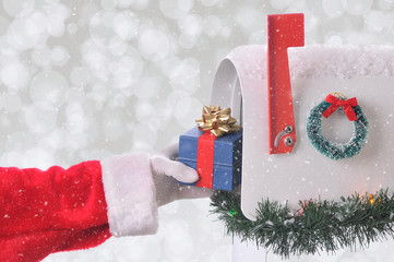 Closeup of Santa Claus placing a small present into an open mail box. Horizontal format wih a silver bokeh background and snow effect.