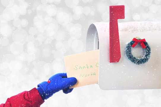 Closeup of a childs hand placing a Letter to Santa Claus in a mail box