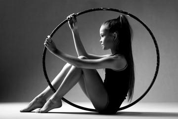 Foto auf Leinwand Gymnastik Portrait of a girl sitting inside a hoop for rhythmic gymnastics. Black background