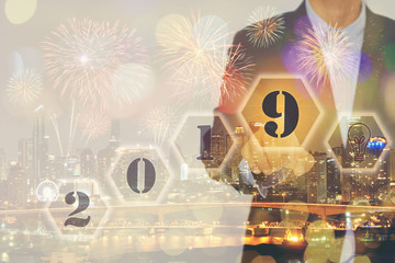 Double exposure of Businessman touching screen with welcome year 2019 on city and brightly colorful fireworks in the evening sky background