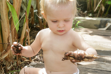 Portrait of adorable blonde baby playing in the garden. Letting your baby get dirty is how baby explores the world and one of the best places to learn that is in the garden.