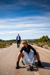 Rocker bride with black leather jacket, boots and sunglasses sitting on a suitcase in the middle of a lonely road and her groom poses behind her.
