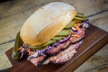 Brisket Sandwich with cucumber and coleslow on cutting board