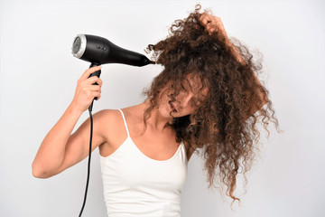 Cheerful lovely young woman in bathrobe standing and drying her curly hair with dryer over white background