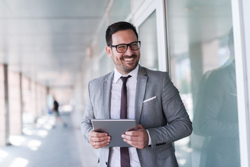Close up of smiling businessman dressed in formal wear using tablet while standing near window outdoors.