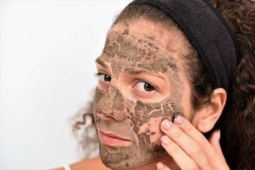 Woman removing facial dried clay mud mask in front of mirror. Skin care. Girl taking care of her complexion. Beauty spa treatment.