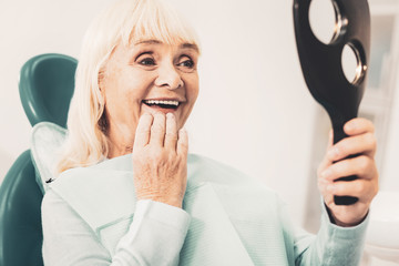 Mature woman with mirror looking at her denture