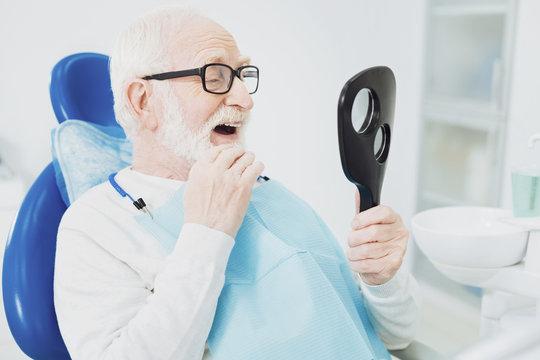 Appealing senior man evaluating his teeth