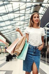 Smiling woman with bags in mall