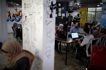 Members of 'We Are Not Numbers' team work on laptops in an office in Gaza City