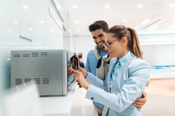 Happy multicultural couple looking for new microwave to buy while standing in tech store.