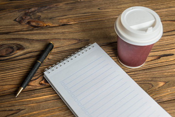 a glass of coffee, a notebook, a pen on the background of a wooden table. lunch break, coffee break