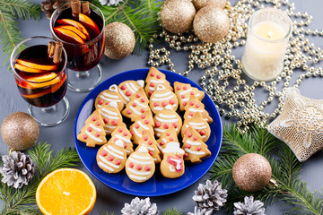 Tasty Christmas cookies, hot mulled wine and decorations with Christmas tree and lights on black background.