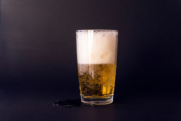 light beer in a glass on a black background