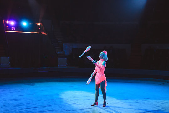 A woman juggles in the circus arena.