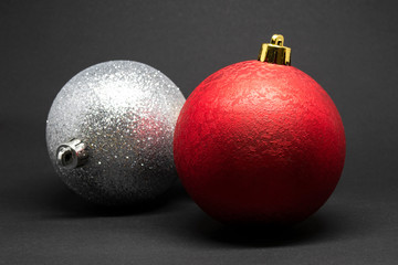 Two Christmas tree decorations isolated on a dark background